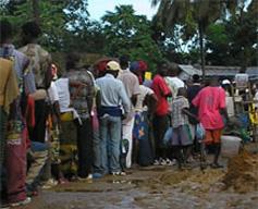 Citoyens libériens pataugeant dans la boue pour aller voter