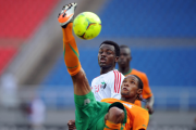 Davies Nkausu of Zambia engages in acrobatics to keep the ball from Sudan's Tahir Mohamed, in white.